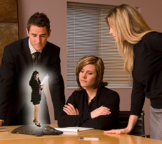 3 office workers having meeting with miniature virtual woman on table device.